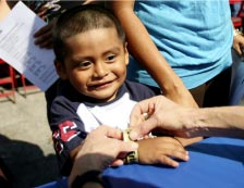 A young Latino boy gets a wristband at CareHarbor